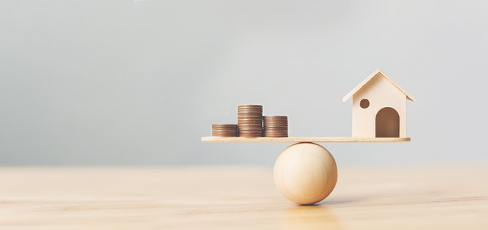 Wooden home and money coins stack on wood scale.