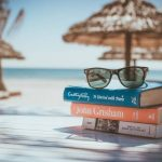 3 books and sunglasses at a beach