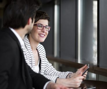 Two business people in office talking