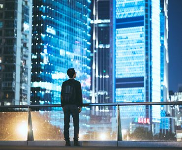 Young man silhouetted against cityscape