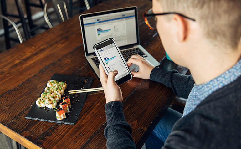 Person using online banking on laptop and mobile in cafe