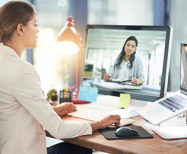 Business woman in one-on-one meeting via computer.