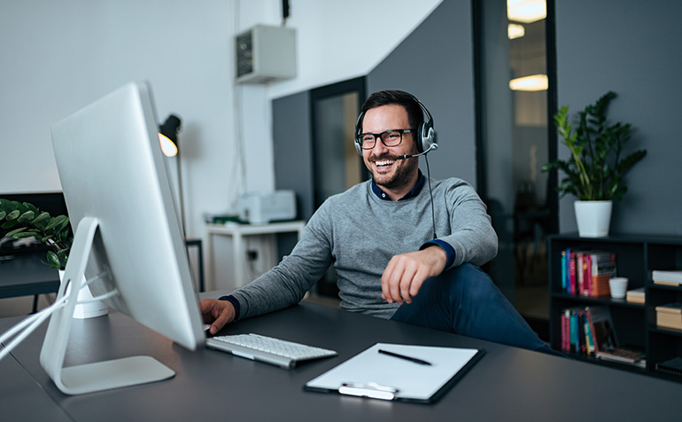 Man with headphones and microphone working from home office.