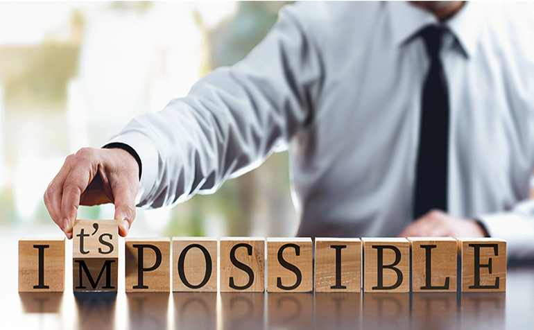 Impossible to it's possible concept with businessman and wooden blocks