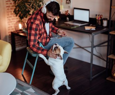 Man working from home office with his dog.