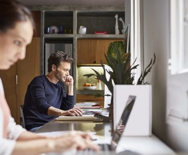 Mid adult man using computer. Woman is working in foreground at desk. Business couple are in home office.