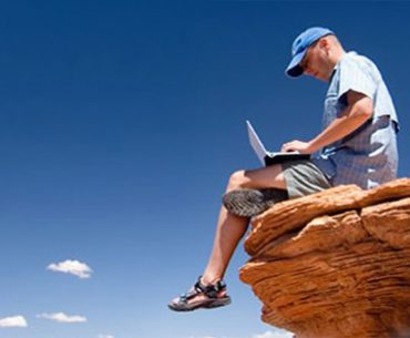 Man working on laptop sitting on edge of rocky outcrop