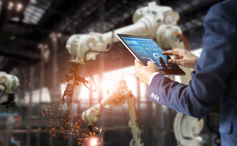 Manager industrial engineer using tablet check and control automation robot arms machine in intelligent factory