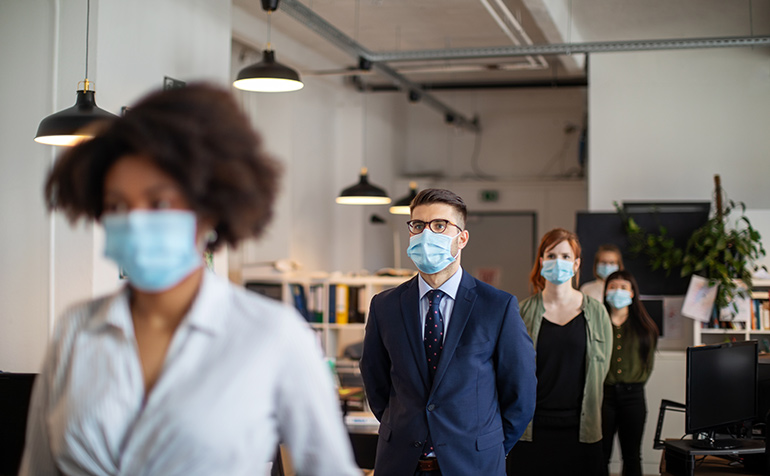 Office workers lined up with surgical masks and safe spacing