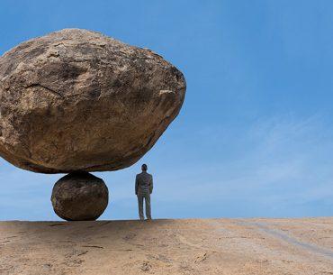 Person standing under balanced rocks