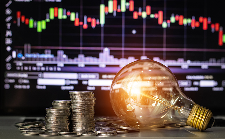 Decorative image: stack of coins & lightbulb in front of business trend graph