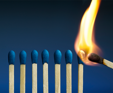 Row of matches with one being ignited - decorative image