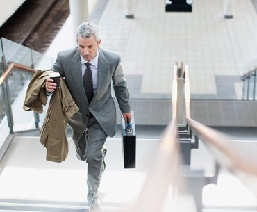Business Man walking up stairs in modern building.