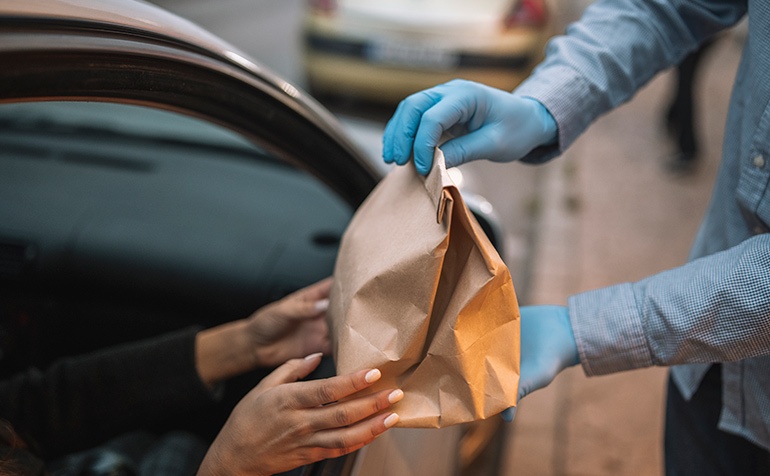 Restaurant meal in paper back being delivered to a driver in a car