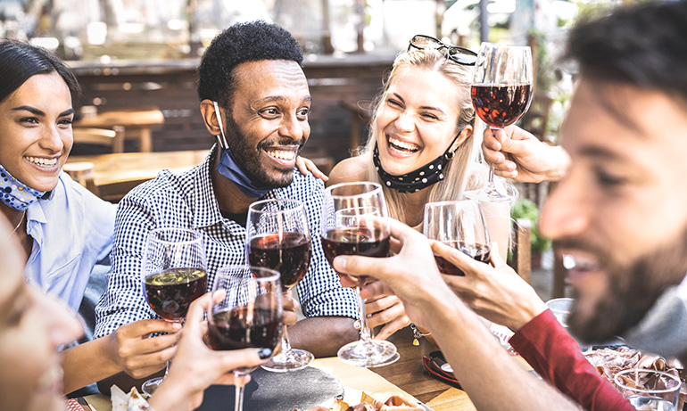 Group of people with face masks pulled down clinking wine glasses