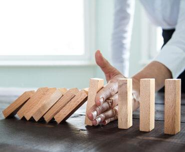 business man stopping blocks falling like dominoes